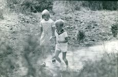 Prince Albert II with a little girl walking in a water steam.