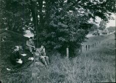 Soldiers sitting together and one of them talking on phone.