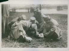 Soldiers surrounding an wounded soldier during first world war, 1915 in Poland.
