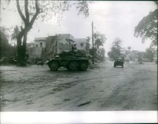 Vehicles in street during wartime.