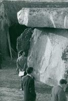 Charles, Prince of Wales, observing a giant rock.