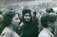 A woman standing amidst the crowd, looking at the camera.