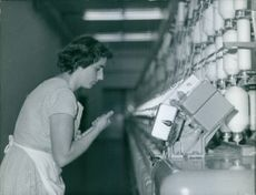 Woman worker standing and looking at machine in the plant.