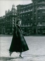 Betsy Blair i Madrid walking alone along wide space fronting building.
