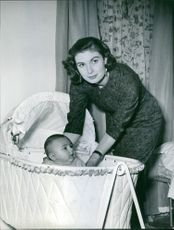 Lynne Russell standing beside her baby and looking towards the camera.