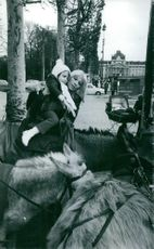Dany Saval picking her daughter up from donkey riding.