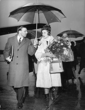 Princess Alexandra walking in the rain, holding flowers, with a man holding an umbrella.