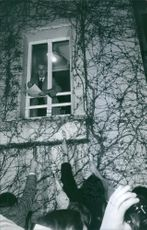 A man looking at the window holding a paper while press people looking at him. March 15, 1971.