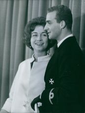 Queen Sofía smiling with Juan Carlos standing beside her. May 15, 1962.