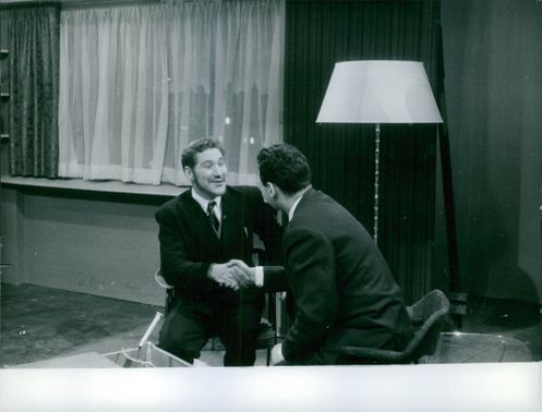 Two men shaking hands while talking to each other and smiling.