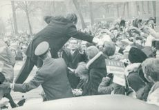 US President Richard Nixon is almost pulled down from his car as he shakes hands with a western climber during the journey through the city