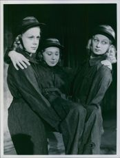 Two girls carrying the girl. 1940.