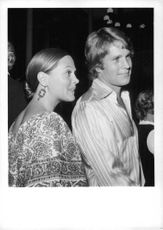 Leigh Taylor Young standing with her husband, talking.