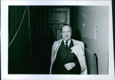A man in suit inside a room.