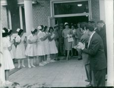 Farah Pahlavi  coming out of a building with a line of nurses and people awaiting to welcome her.