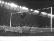 Goalkeeper hanging on the upper bar of the goal during football match.  - 1959