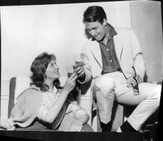 Jacques Charrier enjoying drink with a woman.