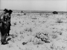 Two soldiers looking at a dead man on the ground in Israel.