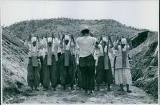 Workers standing holding wooden blocks during training for manual tampering passage way.