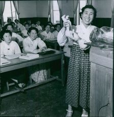 A smiling woman holding the dummy of a newborn baby for demonstration in class.