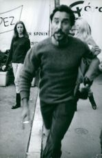 Brigitte Bardot standing and man running in front of her.