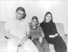 Father and his children sitting on a couch.