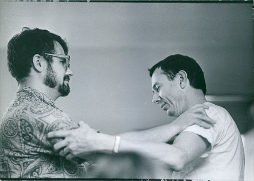 Two men holding each other.