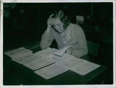 Year ?  A photo of a woman siting and reading papers.