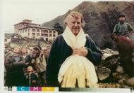 Edmund Hillary, Alpineist and Polar Scientist are welcomed with flower wreaths at Tyangboche Monastery