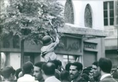 A child dressed as a soldier being lifted up by someone in the crowd gathered on the street.