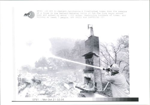 a fire fighter hoses down the remains.