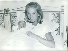 Queen Paola of Belgium smiling with her newborn baby.