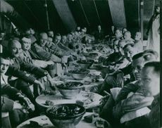 Colonial troops siting together and having a meal.