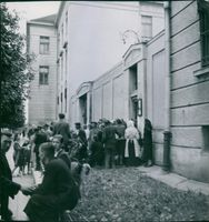 People gathered in street in front of a building in Poland, 1948.