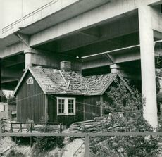 """Sodertalje. A red little cabin that was """"not in the way"""" was left under the new channel bridge"""