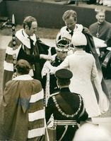 Charles, Prince of Wales with officials putting crown on his head.