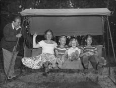 """Johan Jonatan """"Jussi"""" Björling with his wife and kids on a swing."""