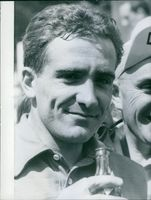 A photo of Roger Rivière a French track and road bicycle racer holding bottle and smiling. 1959.