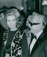 Darryl Francis Zanuck standing with an actress in the hall. 1968