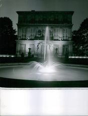 A view of fountain sprays in front of a vintage house during night time.