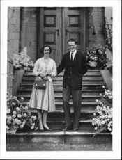 Baudouin and Dona Fabiola standing in front of house.