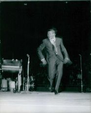 Chubby Checker standing on stage.