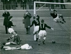 Sportsmen playing football in a ground, photographers taking pictures.