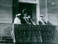 Gustaf V of Sweden standing at the balcony talking to a woman.