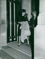 Woman named Soraya with another woman walking out of a building.  Taken - 26 Oct. 1961