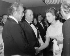 Princess Alexandra handshake with a man, in a gathering.