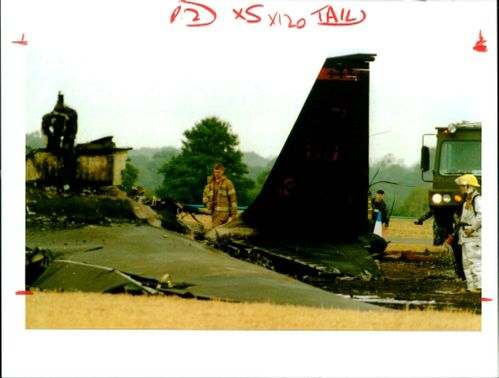 Aircraft crash:fire crew work near tail section of wreckage.