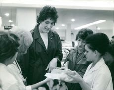 Ravila Salimova being assisted by sales ladies inside a store.  Taken - 1 Oct. 1962