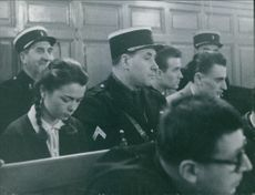 men and women sitting inside of the court room while attentively listening