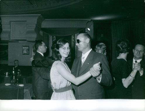 Moshe Dayan is dancing on the dance floor with a lady. 1960